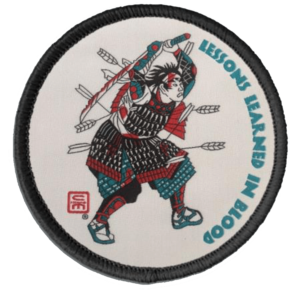 A woven patch with merrow edge showing a Samurai in battle, bloodied and shot full of arrows, with a broken and bloodied sword raised overhead