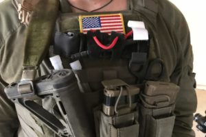 A photo of the burly chest of an operator with an American flag and CAT tourniquet staged on the exterior of his gear, center line